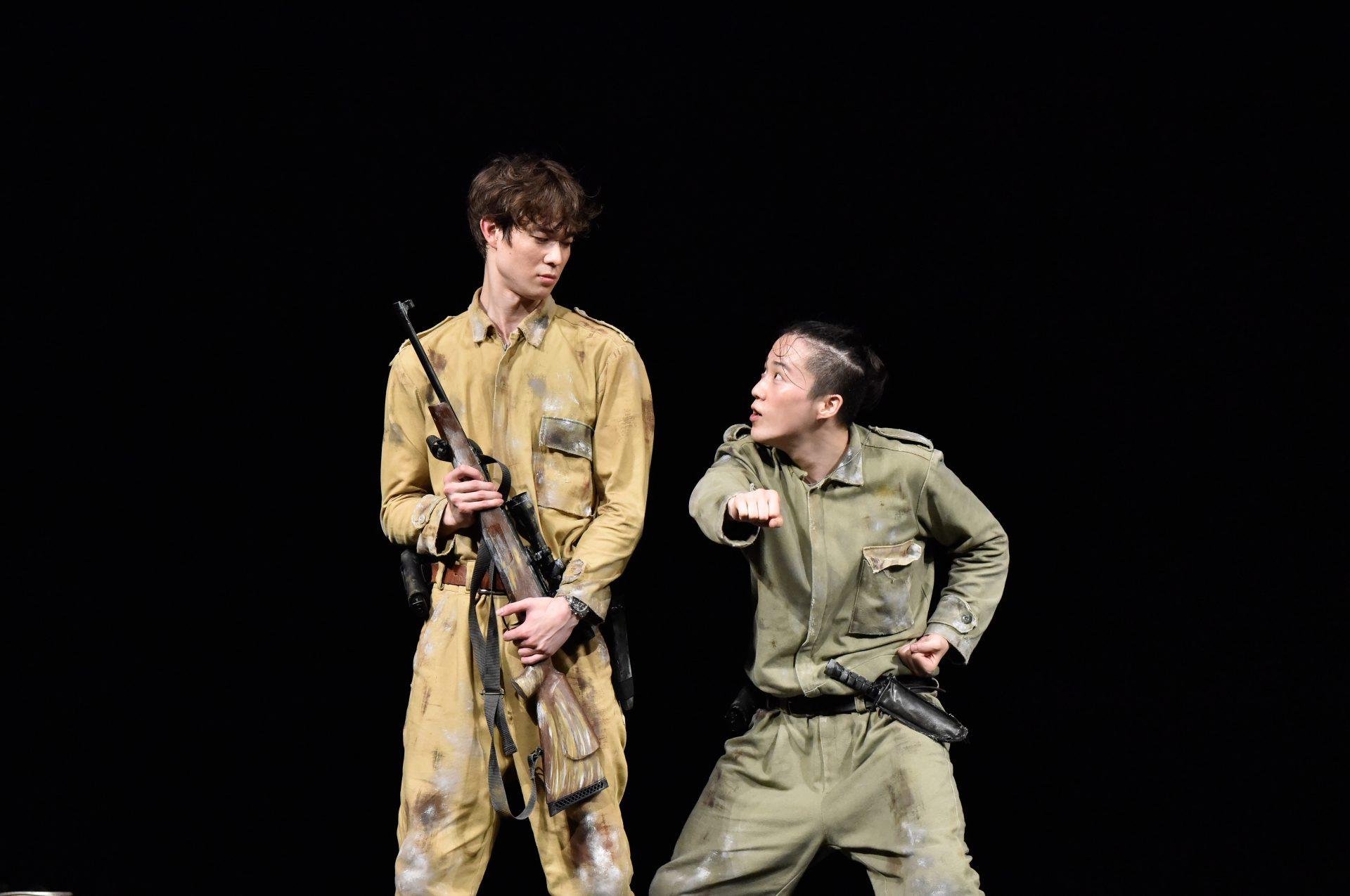 二人の兵士が見つめ合っている。一人は銃を持ち、上から見下ろし、もう一人は低い姿勢で前方に拳を突き出している。