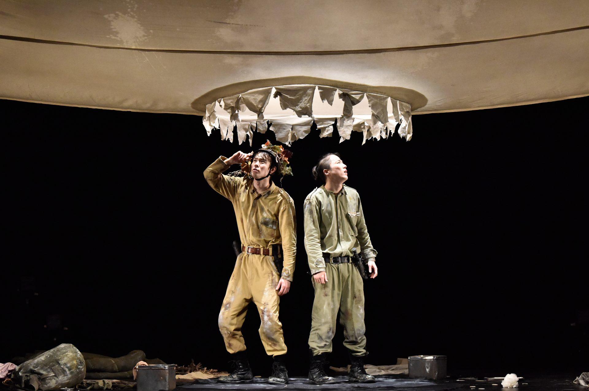 作品メインビジュアル。二人の兵士が、舞台から吊るされた大きな穴の下に立ち、上を見上げている。