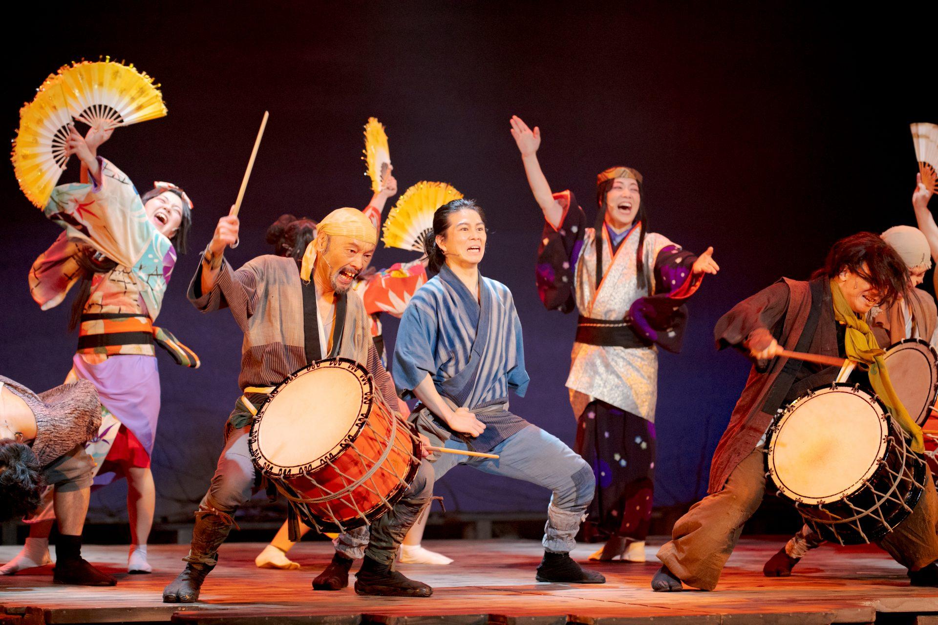 鹿おどりのシーン。太鼓を叩く人、扇子を持って舞う人などが舞台上にいる。