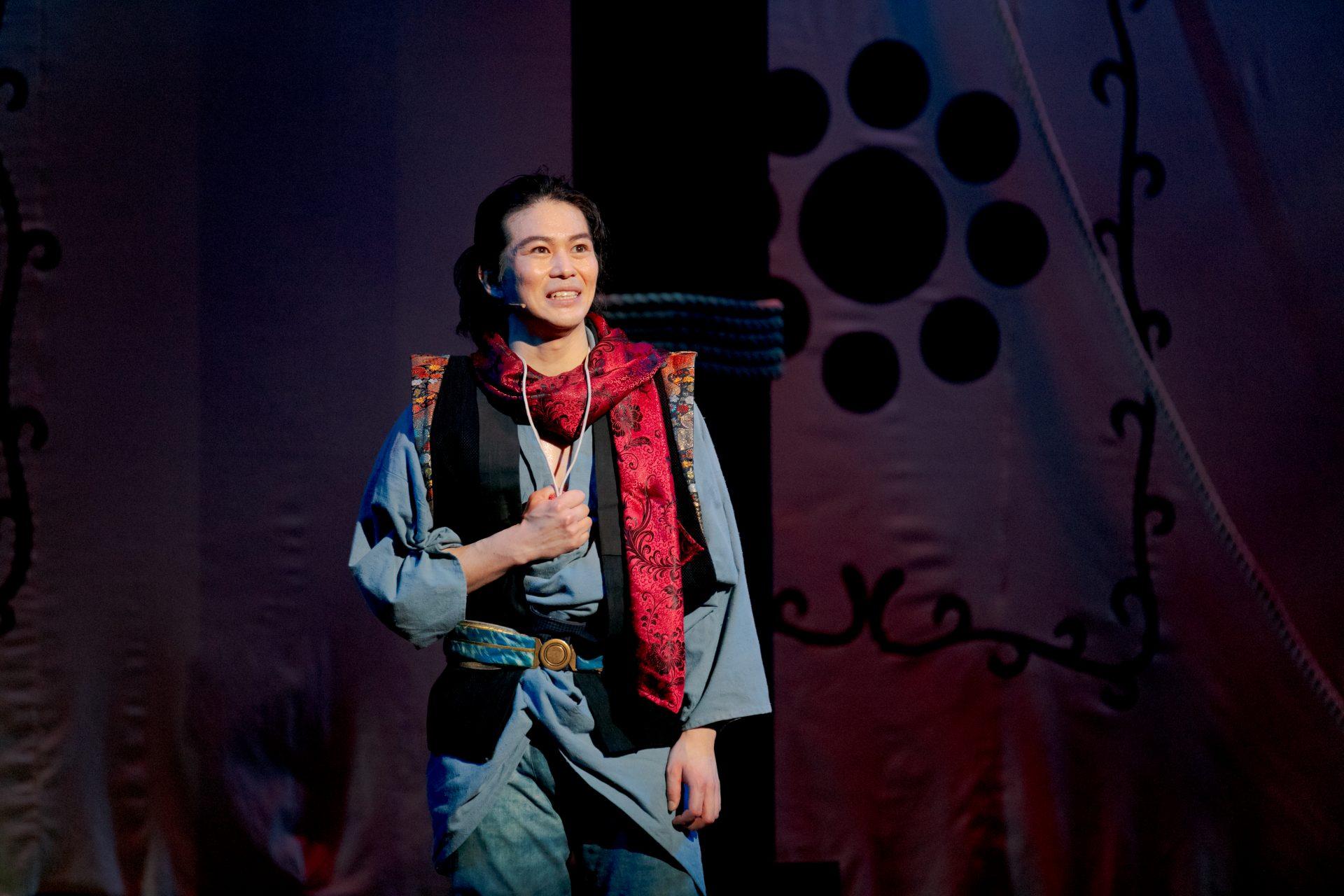 登場人物リウタが舞台上に立っているシーン。青い着物に赤い首巻きを身に着けている。