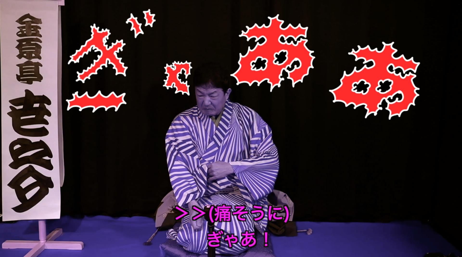 金原亭世之介が舞台で話している。背景に漫画チックな字幕で「ぎゃああ」と表示されている