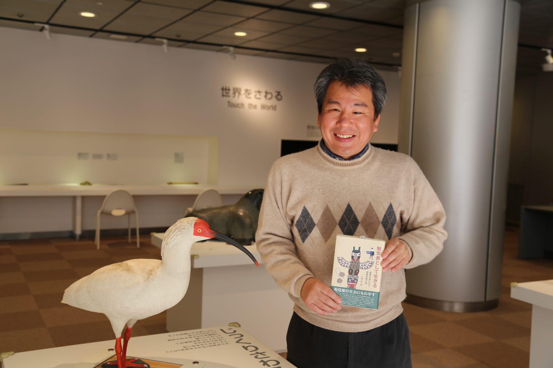 国立民族学博物館の触れるコーナー。鳥のトキの模型の前で、著書を持ってニッコリ微笑む広瀬さんのお写真